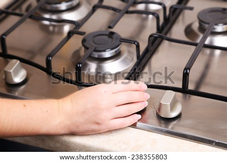 Female hand turn on gas stove - stock photo