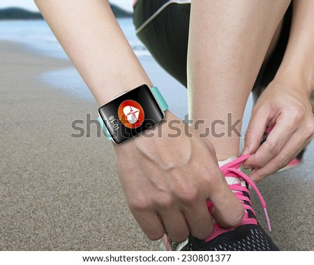 female hand tying shoelaces wearing bright green watchband touchscreen smartwatch with red health icon on natural sea beach background - stock photo