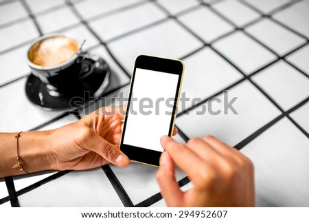 Female hand using a phone with isolated screen on checkered table with coffee cup.  - stock photo