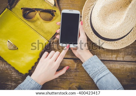 Female hand using mobile phone over old wooden table - stock photo