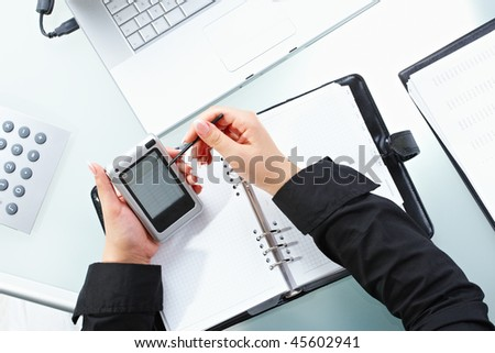 Female hand using touch screen handheld computer with stylus. - stock photo