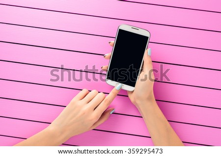 Female hand using white mobile phone over pink background - stock photo