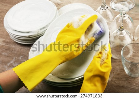 Female hand washing dish close up - stock photo