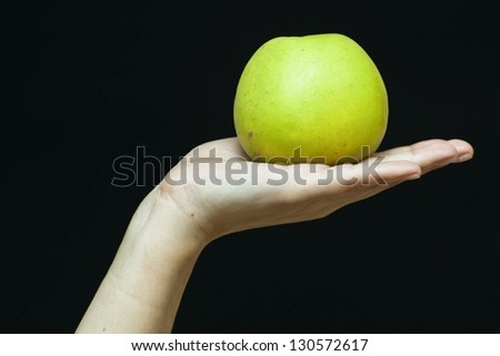 Female hand with a green apple on black background. Health concept - stock photo