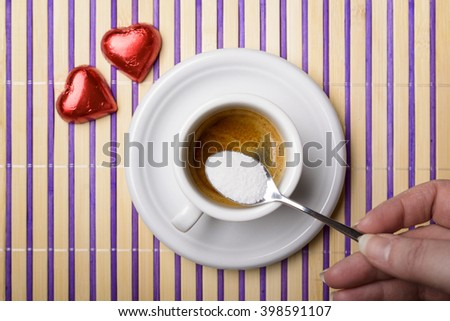 female hand with a teaspoon of sugar to sweeten a cup of coffee and two chocolate heart - stock photo