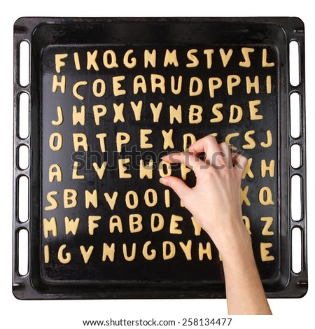 Female hand with alphabet cookie on a baking pan. Cookie making process - stock photo