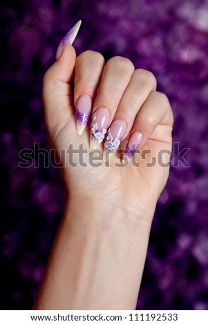 Female hand with beautiful purple manicure - stock photo