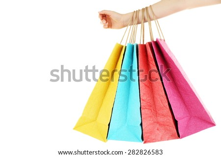 Female hand with colorful shopping paper bags isolated on white - stock photo