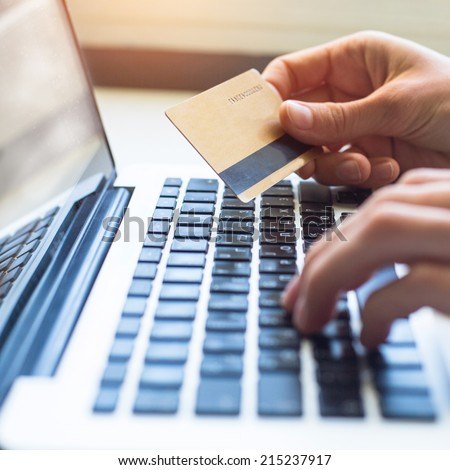 Female hand with credit card and laptop keyboard. Shopping on the Internet. - stock photo
