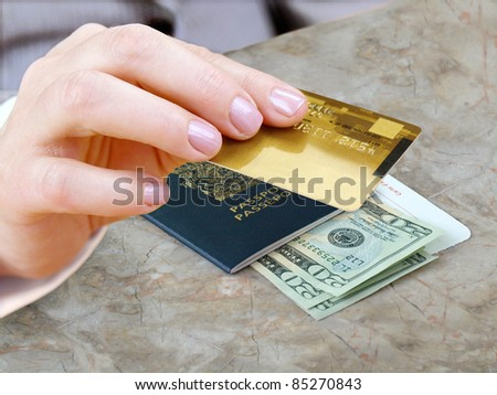 Female hand with credit card and passport, dollars bills on the table. - stock photo
