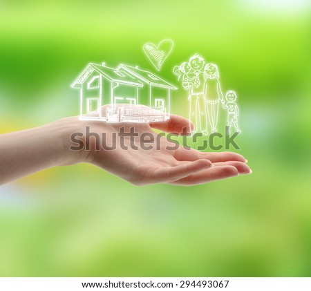 Female hand with drawings of family and house on nature background - stock photo