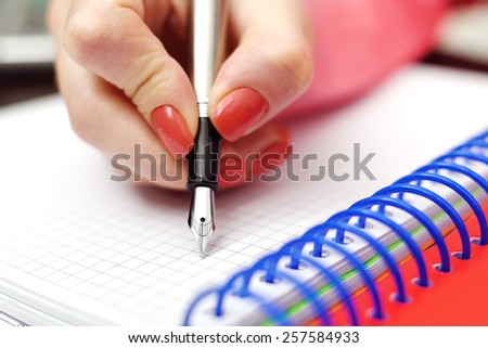 Female hand with ink pen writing in notebook - stock photo