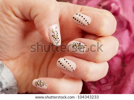 Female hand with nude and black  manicure close up. With dots and  flowers. On the red background. - stock photo