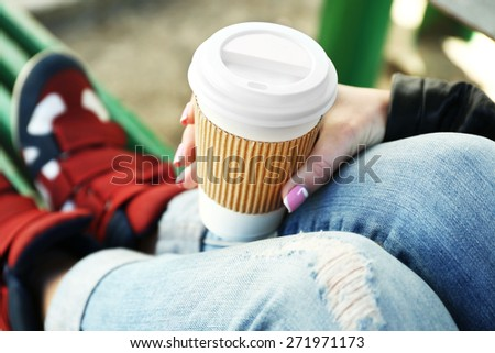 Female hand with paper cup of coffee outdoors, closeup - stock photo