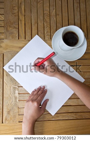 Female hand with pencil writing on a white sheet of paper. Wooden table and a cup of black coffee - stock photo