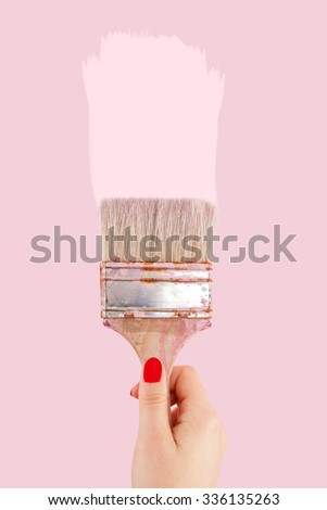 Female hand with red fingernails holding paintbrush isolated on pink background. Creative painting.  - stock photo