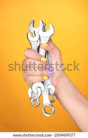 Female hand with stylish colorful nails holding wrench, on color background - stock photo
