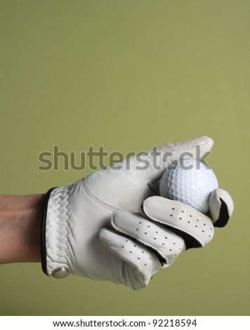 female hand with white glove holding a golf ball - stock photo