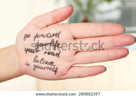 Female hand with written message in room - stock photo