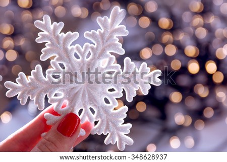 Female hand with xmas snowflake on blurred lights bokeh holiday background. Christmas.