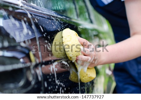 Female hand with yellow sponge washing car - stock photo