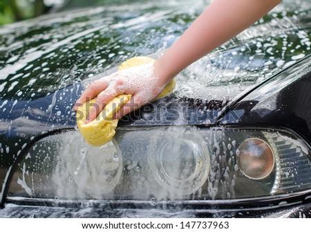 Female hand with yellow sponge washing car - stock photo