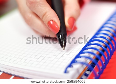 Female hand writing in blank notebook, close up - stock photo