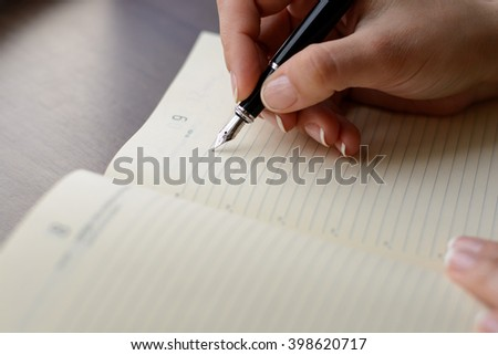 Female hand writing in notebook with pen. - stock photo