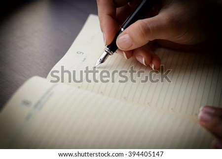 Female hand writing in notebook with pen. Macro with blur and soft focus. - stock photo