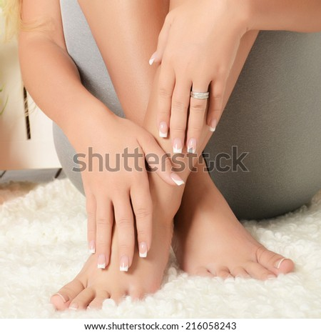 Female hands and feet with manicure and pedicure - stock photo