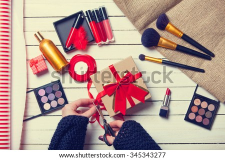 Female hands are wrapping cosmetics in christmas gifts on white wooden background - stock photo