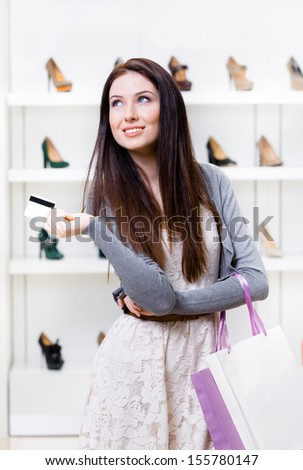 Female hands credit card in footwear shop with great variety of stylish shoes - stock photo