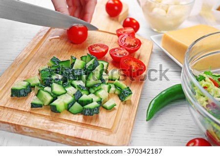 Female hands cutting vegetables for salad, at kitchen - stock photo
