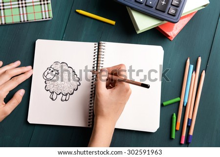 Female hands drawing sheep in notebook on wooden table background - stock photo