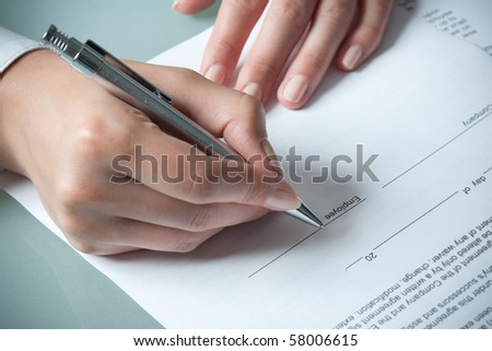 female hands filling out employment agreement contract - stock photo