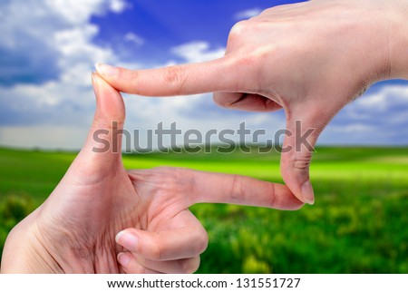 Female hands framing a beautiful spring landscape - stock photo