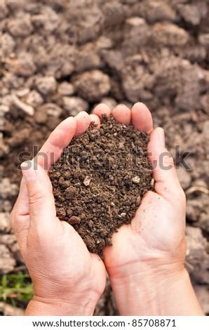Female hands full of soil over soil background.Representing fertility - stock photo