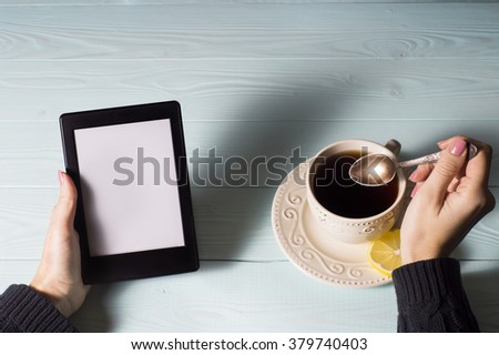 Female hands hold e-book on blue wooden background, flat lay.  - stock photo