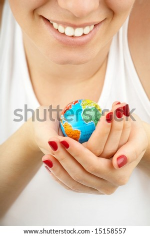 Female hands hold in hands with care a small copy of globe on a white background - stock photo