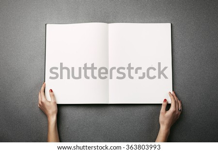 Female hands holding a big open book. Horizontal - stock photo