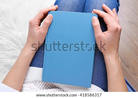 Female hands holding a blue book. - stock photo
