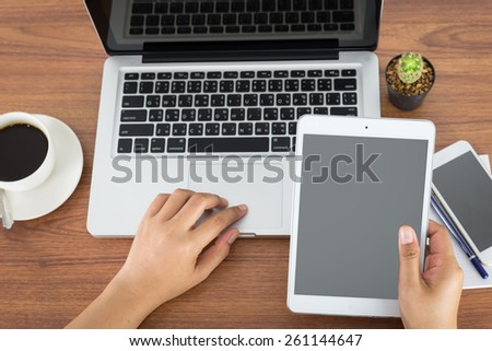 female hands holding a computer tablet and laptop on the table in the office - stock photo