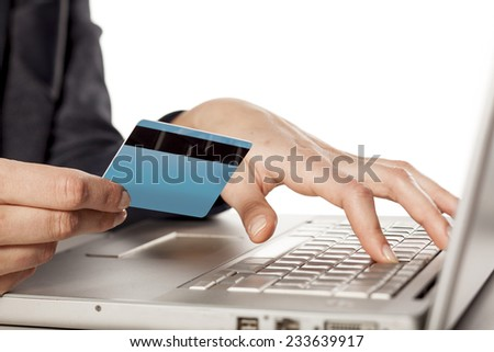 Female hands holding  a credit card and typing on the keyboard - stock photo