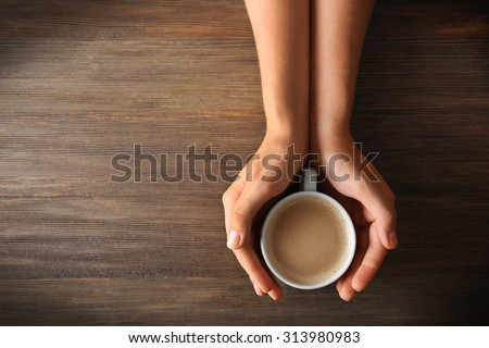Female hands holding a cup of coffee with foam over wooden table, top view - stock photo