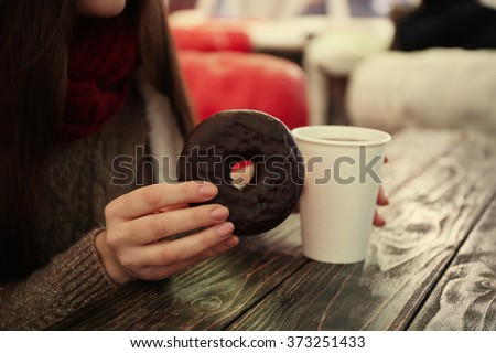 Female hands holding a cup of hot drink and tasty doughnut at the table - stock photo