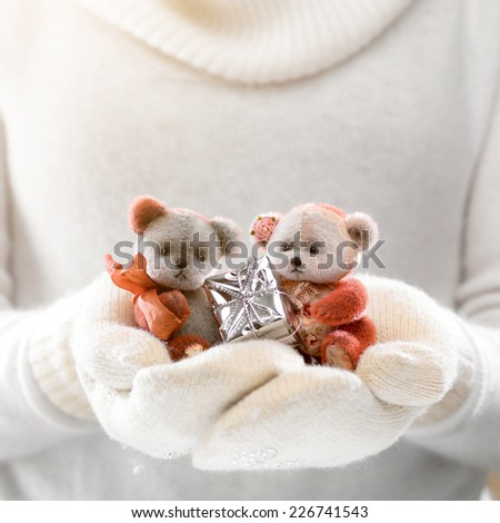 Female hands holding a cute teddy bears with gift. Woman hands in white mittens showing a teddy bear gift. Cute Christmas present. Winter holidays concept.  - stock photo