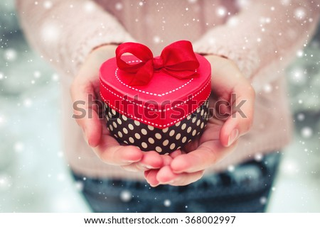 Female hands holding a gift box shaped of heart. The Valentines day and Christmas theme - stock photo