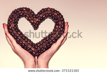 Female hands holding a heart of the coffee beans. Valentine's Day. Be my Valentine. Theme of love, romance, coffee time, cafe. - stock photo