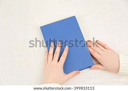 Female hands holding a light-blue book cover  on white desk, top view - stock photo