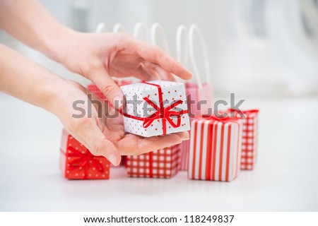 Female hands holding a little gift near red Gift boxes - shopping and holiday concept - stock photo